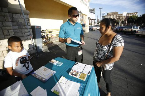Jaime Corona, patient care coordinator at AltaMed, speaks to a woman during a community outreach on Obamacare in Los Angeles, California Nov