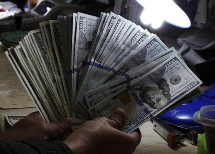 A money changer inspects U.S. dollar bills at a currency exchange in Manila January 15, 2014. REUTERS/Romeo Ranoco