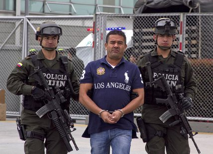 Colombian alleged drug trafficker Diego Perez Henao is escorted by policemen before being extradited from Bogota August 28, 2013. REUTERS/In