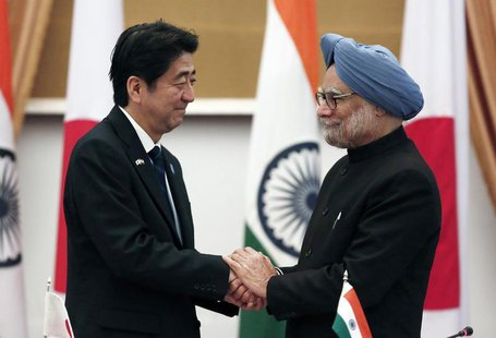 Japan's Prime Minister Shinzo Abe (L) and his Indian counterpart Manmohan Singh shake hands after addressing the media at Hyderabad House in