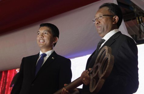 Madagascar's newly elected President Hery Rajaonarimampianina (R) receives the key symbolising the transfer of power from outgoing president