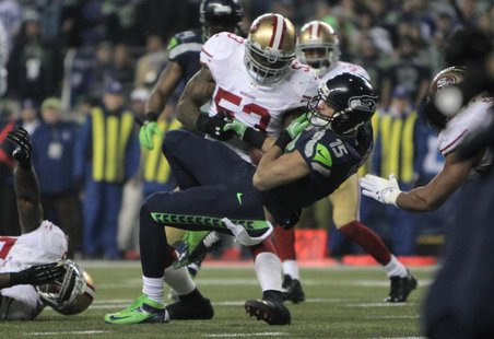 Seattle Seahawks Jermaine Kearse falls on the leg of San Francisco 49ers NaVorro Bowman injuring his knee as he loses control of the ball du