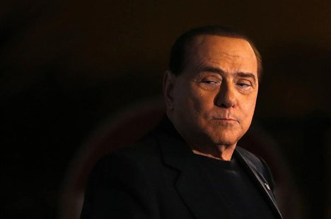 Italy's former Prime Minister Silvio Berlusconi looks on during a speech from the stage in downtown Rome in this November 27, 2013 file phot