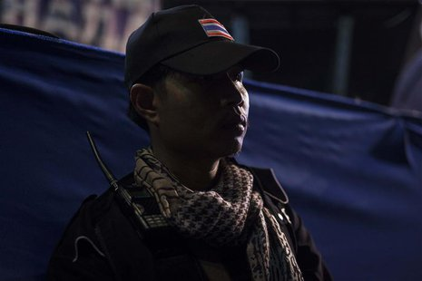 A guard from the anti-government protesters guards the stage as protest leader Suthep Thaugsuban speaks to his supporters during a rally in