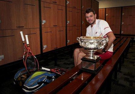 Stanislas Wawrinka of Switzerland sits with the Norman Brookes Challenge Cup in the locker room after defeating Rafael Nadal of Spain in the