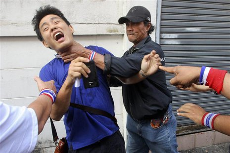 Anti-government protesters attack a voter near a polling station in Bangkok January 26, 2014. REUTERS/Stringer