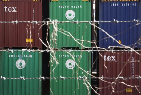 Containers are seen through a steel fence at a port in Tokyo February 20, 2013. REUTERS/Yuya Shino