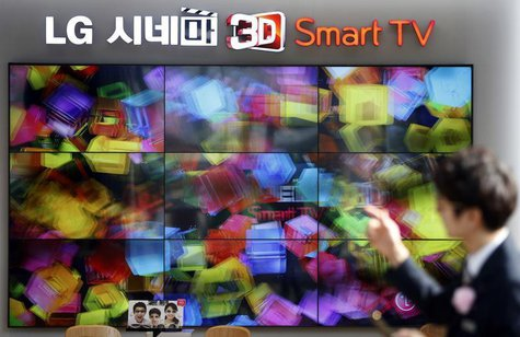 An employee works in front of LG Electronics' 3D TV sets which are made with LG Display flat screens at its store in Seoul January 23, 2014.