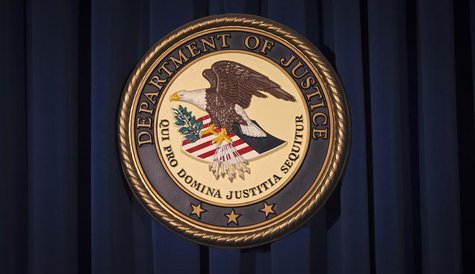 The Department of Justice (DOJ) logo is pictured on a wall after a news conference to discuss alleged fraud by Russian Diplomats in New York