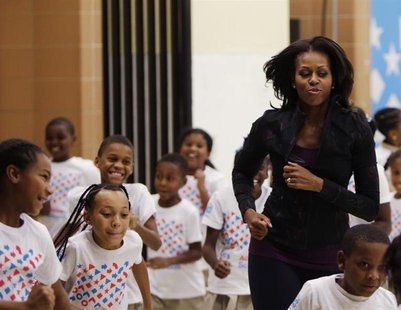 U.S. First Lady Michelle Obama jogs with children at a back-to-school event at Orr Elementary School in Washington September 6, 2013. REUTER