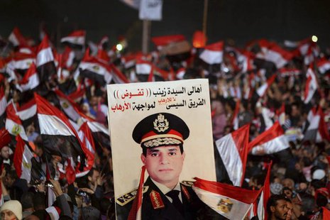 Supporters of Egypt's army chief General Abdel Fattah al-Sisi holds a poster of Sisi in Tahrir square in Cairo, on the third anniversary of