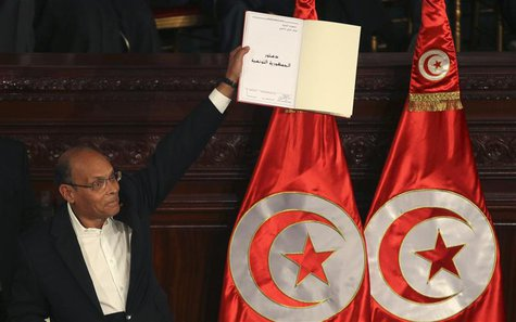 Tunisian President Moncef Marzouki holds a copy of the country's new constitution after signing it in Tunis January 27, 2014. Marzouki and t