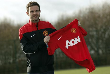 Manchester United's new signing Juan Mata holds a club shirt during a photocall at the club's Carrington training complex in Manchester, nor