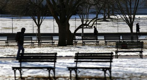 Pedestrians make their way past vacant benches in snowy Lafayette Park in front of the White House in Washington January 27, 2014. REUTERS/K