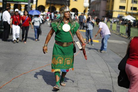 A man dressed as a native Inca walks as he watches the final ruling court session of a decades-old maritime dispute between Peru and Chile,