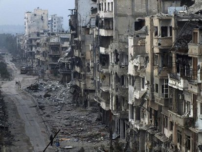 People stand on a street lined with damaged buildings in the besieged area of Homs January 27, 2014. REUTERS/Yazan Homsy