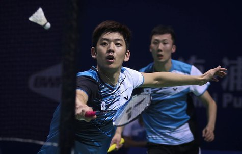 South Korea's Lee Yong-dae (L) hits a return next to his partner Yoo Yeon-seong during their men's doubles semi-final match against Japan's