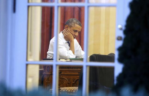 U.S. President Barack Obama sits inside the Oval Office as he prepares for Tuesday night's State of the Union Address to the nation on Capit