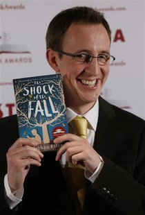 "Shortlisted author Nathan Filer poses for a photograph with his book ""The shock of the Fall"" before the announcement of the winner of the Co"