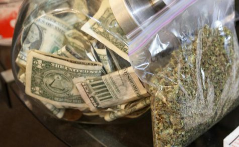 A bag of marijuana being prepared for sale sits next to a money jar at BotanaCare in Northglenn, Colorado December 31, 2013. REUTERS/Rick Wi