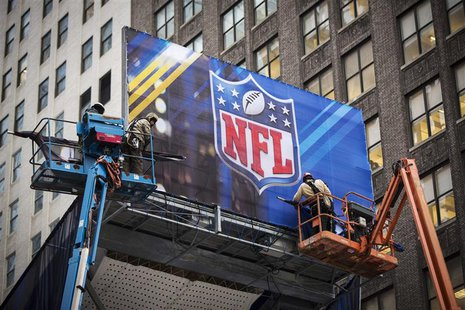 Workers hang signage on a booth on Broadway as preparations continue for Super Bowl XLVIII in New York January 28, 2014. REUTERS/Lucas Jacks