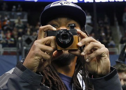 Seattle Seahawks cornerback Richard Sherman takes some pictures as he arrives for Media Day for Super Bowl XLVIII at the Prudential Center i
