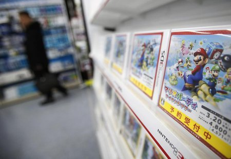 A man looks at items and accessories for Nintendo Co's Wii U game consoles, as its 3DS portable game console software are displayed at an el