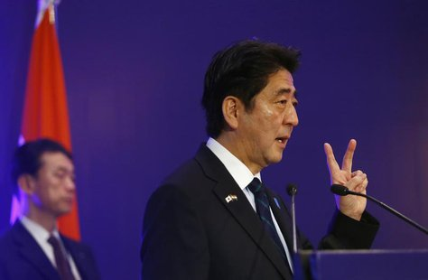 Japan's Prime Minister Shinzo Abe shows a sign as he speaks at a business meeting organised by Confederation of Indian Industry (CII) in New