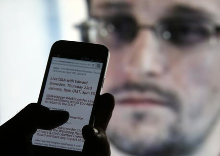 A man uses his cell phone to read updates about former U.S. spy agency contractor Edward Snowden answering users' questions on Twitter in th