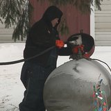 A worker fills a propane tank on Monday, Dec. 23, 2013. (Photo from FOX 11).