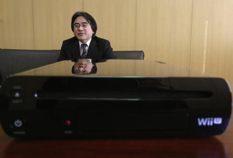 Nintendo Co's President Satoru Iwata speaks next to the company's Wii U game console during an interview with Reuters at the company headqua