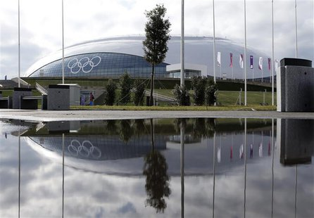 The Bolshoy Ice Dome is reflected in a puddle of water on the Olympic Park as preparations continue for the Sochi 2014 Winter Olympics, Janu