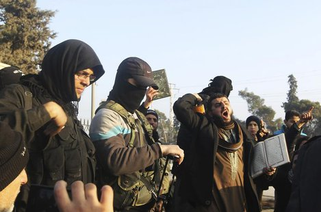 Fighters from the Islamic State in Iraq and the Levant (ISIL) try to calm civilians demonstrating against the rebel infighting in Aleppo Jan