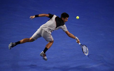 Novak Djokovic of Serbia hits a return to Stanislas Wawrinka of Switzerland during their men's singles quarter-final tennis match at the Aus