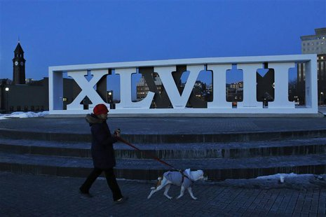 A woman walks with her dog next to roman numerals for NFL Super Bowl XLVIII football game in Hoboken, New Jersey, January 30, 2014. REUTERS/