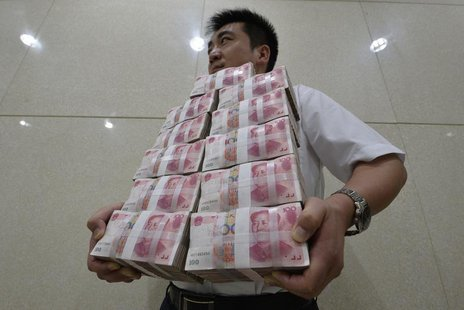 An employee carries bundles of 100 yuan Chinese bank notes to store after counting at a bank in Taiyuan, Shanxi province July 4, 2013. REUTE