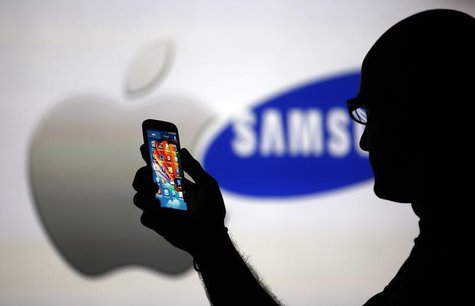 A man is silhouetted against a video screen with Apple and Samsung logos as he poses with a Samsung Galaxy S4 in this photo illustration tak