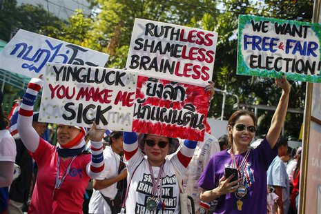 Anti-government protesters hold placards during a march through central Bangkok January 30, 2014. REUTERS/Athit Perawongmetha