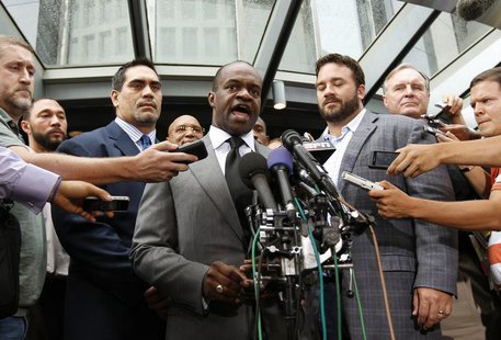 Executive director of the NFL Players Association DeMaurice Smith (C) speaks outside the NFL Players Association Headquarters in Washington