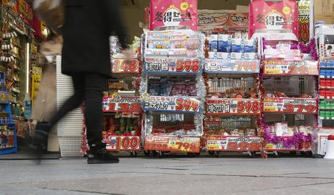 A pedestrian walk past a discount shop in Tokyo November 29, 2013. REUTERS/Yuya Shino