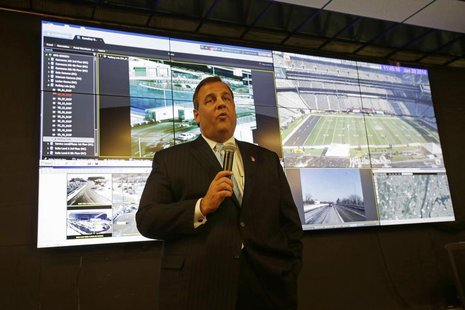 New Jersey Gov. Chris Christie speaks in front of a group of monitors as he visits the Super Bowl security operations center in East Rutherf