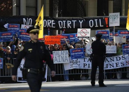 Protesters against the proposed Keystone pipeline hold placards across the street from where U.S. President Barack Obama was to hold a Democratic Party fundraiser, in San Francisco November 25, 2013.  CREDIT: REUTERS/JASON REED