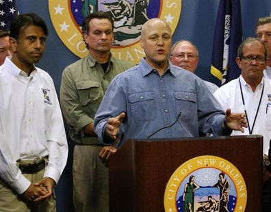 New Orleans Mayor Mitch Landrieu talks about Tropical Storm Isaac as Louisiana Governor Bobby Jindal (L) looks on during a news conference a