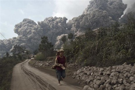 A villager run as Mount Sinabung erupt at Sigarang-Garang village in Karo district, Indonesia's North Sumatra province, February 1, 2014. RE