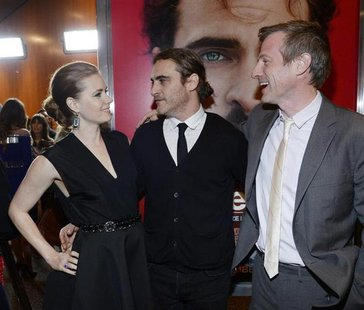"Cast members Amy Adams and Joaquin Phoenix stand next to writer/director Spike Jonze at the film premiere of ""Her"" at the Directors Guild of"