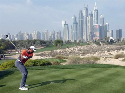Tiger Woods of the U.S.takes a shot on the 8th tee during the third round of the 2014 Omega Dubai Desert Classic in Dubai February 1, 2014.