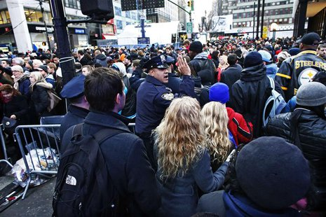 A New York Police officer tries to control the massive traffic of fans while they gather en masse at Super Bowl Boulevard zone ahead of Supe
