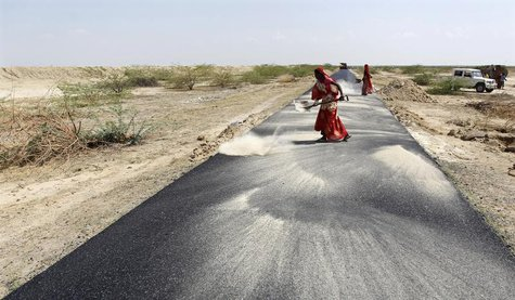 Women labourers throw dust on a road tarmac under construction at Bharadva village in the western Indian state of Gujarat April 23, 2013. RE