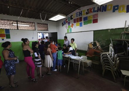 Voters wait in line to cast their votes in the presidential elections at a polling station outside in San Salvador February 2, 2014. REUTERS