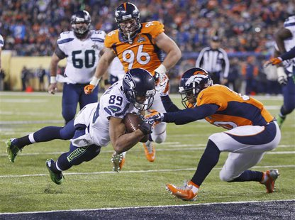 Seattle Seahawks wide receiver Doug Baldwin (89) dives into the end zone for a touchdown past Denver Broncos free safety Mike Adams during t